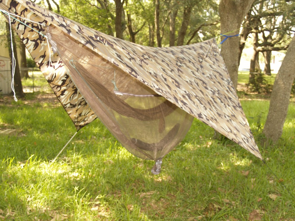 Hammock rain fly in use showing mosquito netting, hammock and gear sling hanging below.